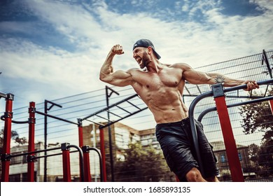 Bearded bodybuilder man exercising on monkey bars for the upper-body in a modern calisthenics park outdoors on a sunny day. Show biceps and scream for motivation.
