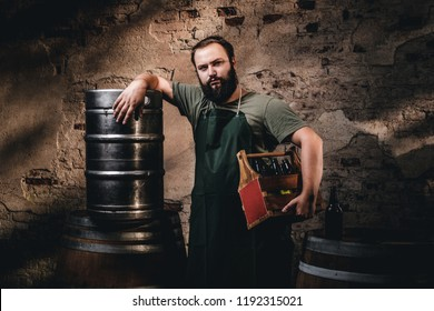 Bearded brewer in apron holds the wooden box with beer while standing near barrels at brewery factory.