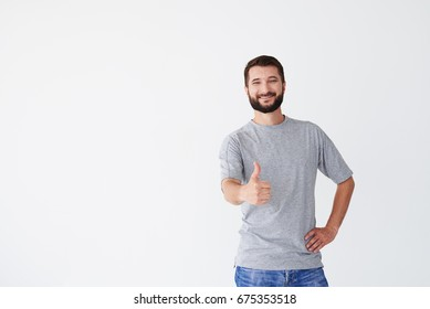 Bearded brunet in front of white background, holding right hand thumb up, smiling person mid shot