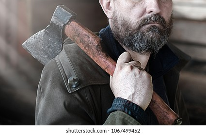 a bearded brunette man with  gray hair  with an ax in his hands in a wooden log hut