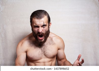 Bearded, brutal man on a plain background. Viking (barbarian).