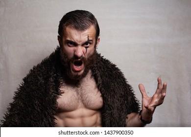 Bearded, brutal man on a plain background. Viking (barbarian).