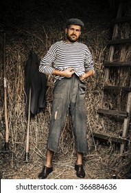 bearded brutal man peasants torn old clothes and a cap with sharp pitchforks throws hay in the barn and drinking alcohol from a bottle