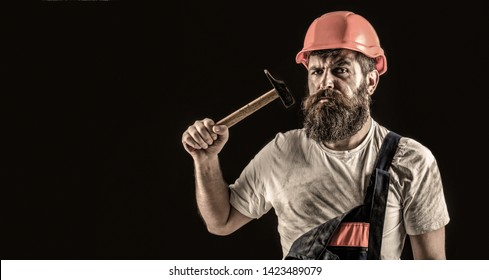 Bearded builder isolated on black background. Bearded man worker with beard, building helmet, hard hat. Hammer hammering. Builder in helmet, hammer, handyman, builders in hardhat. Copy space.