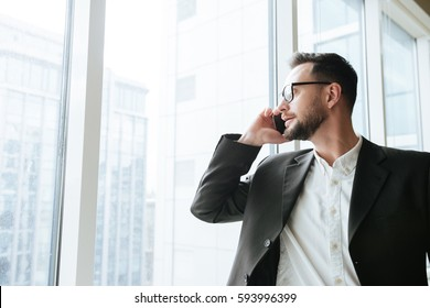 Bearded business man in suit and eyeglasses which talking on phone and looking away near the window