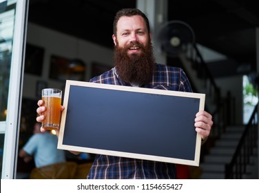 bearded business owner standing with sign and holding beer in front of brew pub
