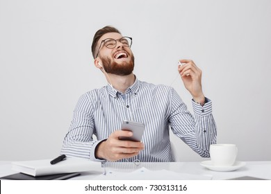 Bearded businessman can`t stop laughing as listens to anecdotes or jokes with earphones, isolated over white background. Overjoyed hipster guy sits at working desk, uses modern smart phone, headphones
