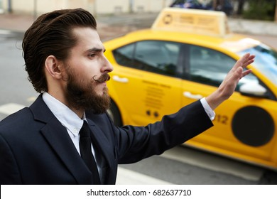 Bearded businessman catching taxi by road