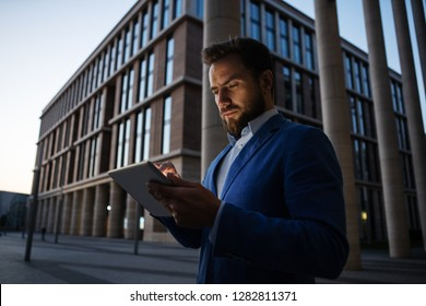 Bearded businessman in formal suit browsing tablet on street with contemporary architecture