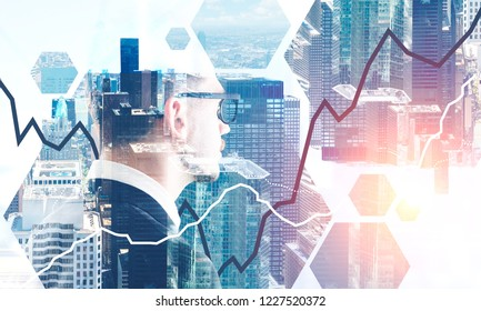 Bearded businessman in glasses looking at modern cityscape with graph in the foreground. Toned image double exposure