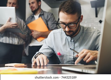 Bearded businessman in glasses uses a computer tablet. Teamwork on a new startup. Business analysts. Coworking in a modern loft space using electronic devices