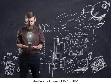 A bearded businessman holding a light bulb. Business doodles drawn on a blackboard behind. 3d render elements in collage