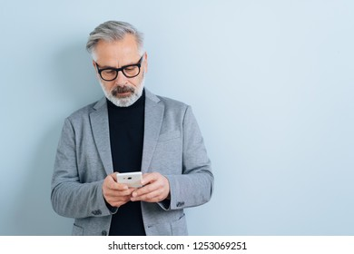 Bearded businessman texting a message on a mobile phone with alook of concentration in front of a white wall and copy space