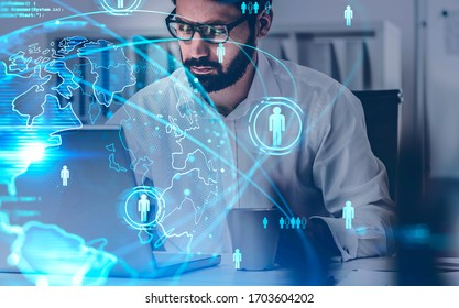 Bearded businessman using laptop in blurry office with double exposure of blurry social network interface. Concept of HR and recruitment. Toned image