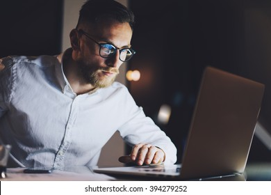 Bearded businessman wearing white shirt, glasses working on modern loft office at night. Man using contemporary notebook texting message, blurred background. Horizontal, film effect, bokeh