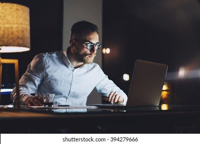 Bearded businessman wearing white shirt working on modern loft office at night. Man using contemporary notebook texting message, blurred background. Horizontal, film effect, bokeh