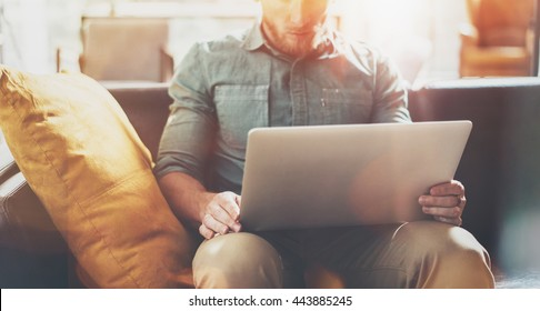 Bearded Businessman work Laptop modern Design Interior Loft Studio Place.Man relaxing Vintage Sofa.Use contemporary Notebook Send Message.Blurred background.Creative Process Startup Idea.Film effect