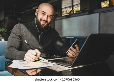 Bearded businessman is working on laptop,making notes in document,speaks in headphones on cell phone while sitting at table in coffee shop.Freelancer works remotely.Online marketing,business education