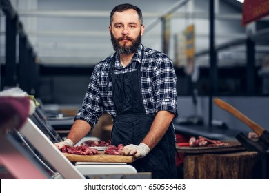 Bearded butcher dressed in a fleece shirt serving fresh cut meat in a market.