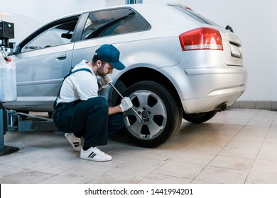 bearded car mechanic in uniform changing car tire in car service