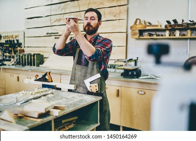 Bearded carpenter enjoying hobby working process at his workstation of manufacturing, side view of skilled self employed artisan in apron checking element for handmade construction of wooden plank