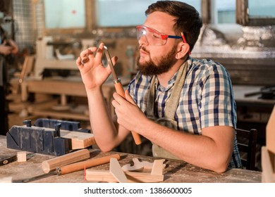 Bearded carpenter holding a chisel standing in the home workshop