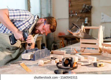 Bearded carpenter with safety glasses drills wooden bar