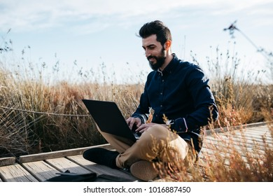 Bearded casual man relaxing on pathway in dry rural fields surfing laptop in sunlight looking happy.