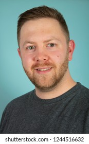 Bearded casual young man in a grey t-shirt looking pensively at the camera. A close up frontal studio portrait.