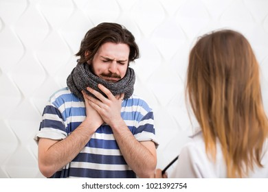 Bearded caucasian ill teenager with gray scarf around the neck visits the doctor