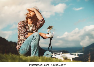 A bearded Caucasian man with a curly hair is sitting outdoors in the mountain, holding the remote controller from his drone, and looking around to check out the weather before launching the quadcopter