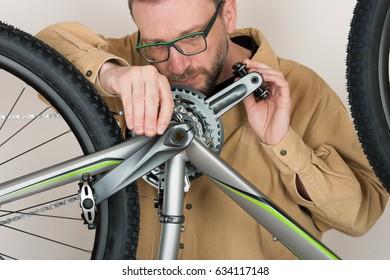 Bearded caucasian man repairing the mtb bicycle.