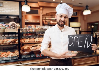 A bearded chef in a hat shows his hand on a plate openly. A large selection of excerpts in the store of fresh excerpts.