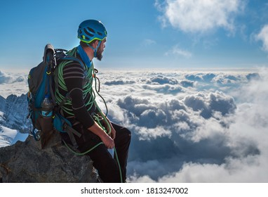 Bearded Climber in a safety harness, helmet, and on body wrapped climbing rope with sitting at 3600m altitude on a cliff and looking at  picturesque clouds during Mont Blanc ascending, France route
