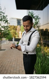 Bearded dapper Arabic muslim businessman rolling up shirt sleeve after busy work day waiting for lift