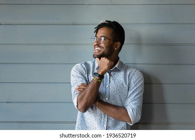 Bearded dreamer. Smiling millennial afro american man hipster in stylish glasses posing against grey wall look away. Confident motivated young black guy dream think feel hopeful optimistic. Copy space