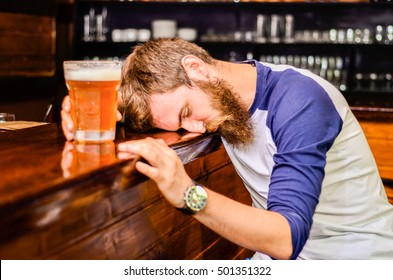 bearded drunk man sleeps with Barney table with a glass of beer