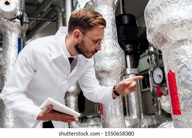 bearded engineer in white coat holding digital tablet and pointing with finger at air supply system