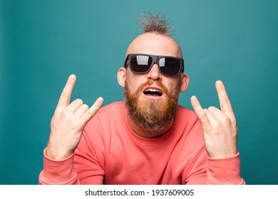 Bearded european man in casual peach isolated on turquoise background  shouting with crazy expression doing rock symbol with hands up