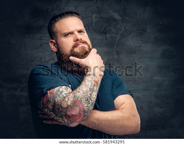 Bearded fat male with tattoo on arms posing over grey background.