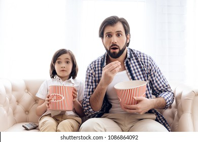 Bearded father with small son is watching thrilling film, eating popcorn. Hilarious pastime.
