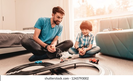 Bearded Father and Son Playing with Toy Race Road. Man Sitting on Floor. White Carpet in Room. Toy Cars. Exited Boy. Happy Family Concept. White Carpet. Lying on Floor. Indoor Fun.