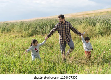 Bearded father walking with her daughter and son in spring day