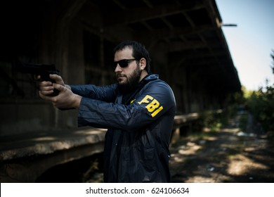 Bearded FBI agent in action with a gun outdoors