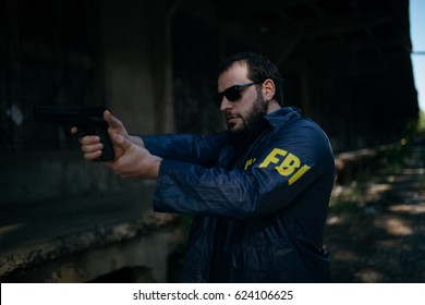 Bearded FBI agent with a gun on a mission outdoors