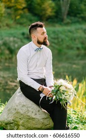Bearded fiance in a white shirt with a bouquet of dreams