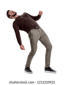 A bearded fit man in casual clothes stands with his back deeply bent backwards on a white background. Loss of position. Falling man. Risky move.