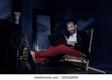 Bearded Freelancer Behind the Laptop in a Cheerful Mood. A Man Looks At 40 Years. He is Wearing a Black Jacket and Red Pants.