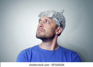 Bearded funny man in a cap of aluminum foil. Concept art phobias