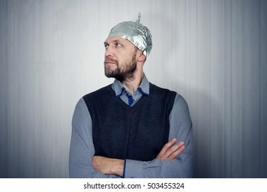 Bearded funny man in a cap of aluminum foil. Concept art phobias